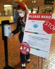A volunteer uses a hand sanitizer station at Southern State Community College in Hillsboro.