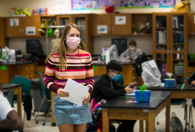 Ellie Horvath, 17, a senior at Mason High School, turns in a test during Honors Anatomy, Wednesday, Oct. 7, 2020. Horvath was forced to quarantine and miss eight days of in-school learning in September because she was exposed to COVID-19. She did not get the virus. But the missed time at school meant she missed the senior night and a big cross-country invitational.