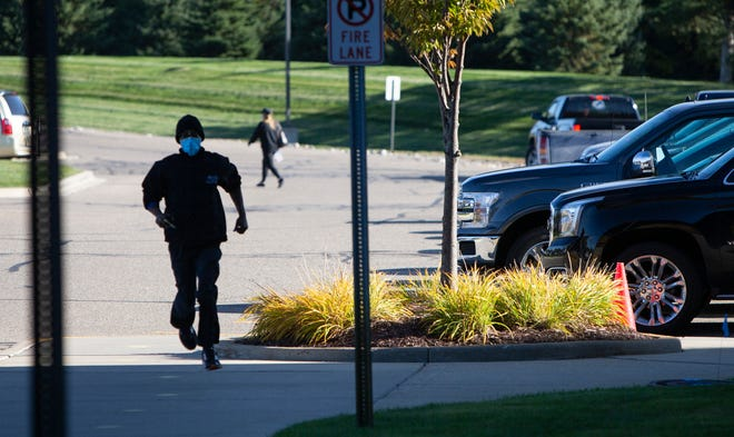 Henry Ford West Bloomfield Hospital valet employee Kenneth Douglas, 31, of West Bloomfield, runs back to the main entrance after parking a car on Oct. 8, 2020. Douglas said a pay increase may relieve him of having to hold two jobs to make ends meet.