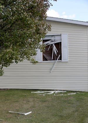 The home in Hartland Township of one of six people charged in an alleged plot to kidnap Michigan Governor Gretchen Whitmer. The home in Hartland Meadows is seen on Oct. 8, 2020, had four vehicles in the driveway and one window showed signs of damage with broken glass, window blinds on the grass in front of the house and brown tarp covering where the glass was.