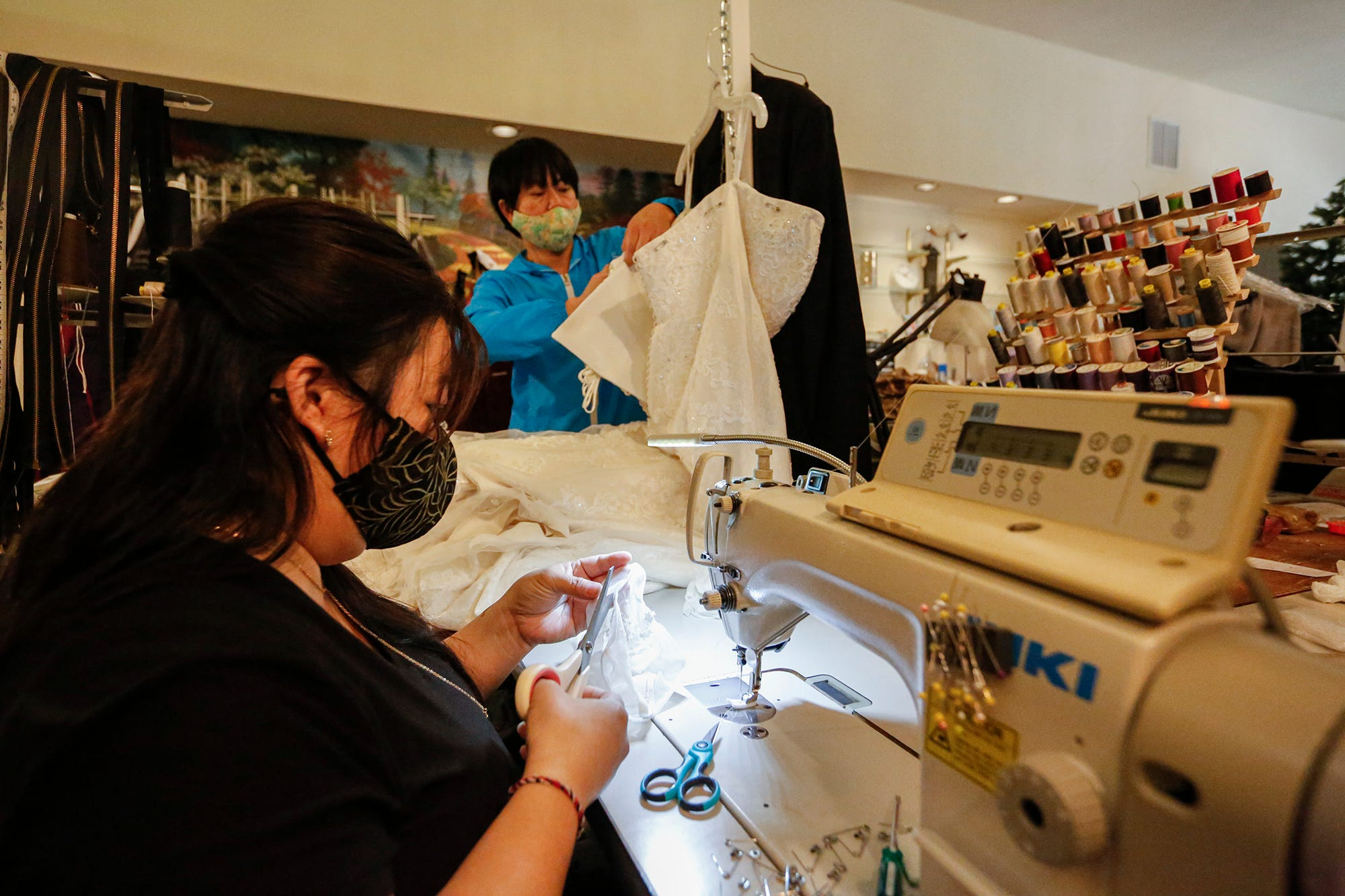 Bao and Soua Xiong of S&B Alterations work on dresses  at their shop at 47 S. Main Street in Fond du Lac. The business has been inundated with a backlog of wedding dress alterations that were previously on hold because of COVID-19 restrictions.