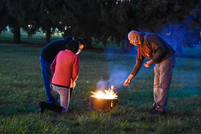 Kathy Whisler, Scout Shawn Stonerook, and Scout Leader Mike Showman roast s'mores over a fire during a meeting in the shelter house at Hayes Memorial Methodist United Methodist Church.
