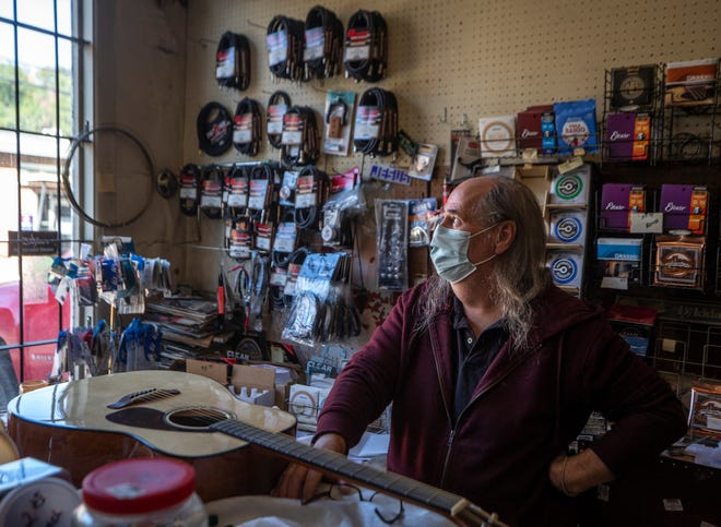 """Philip Stidham looks out the window of Taulbee's Music, which has been in business in downtown Hazard, Kentucky for over 50 years. He says the economy in Hazard is slow. """"You don't see the people out as much as you used to."""" He hopes for the price of coal to start picking back up soon."""