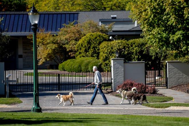 James McClurken walks dogs past Gov. Whitmer's residence on Thursday, Oct. 8, 2020, in Lansing.