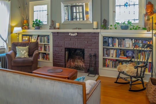 The living room is anchored by a beautiful fireplace and built-in bookcases.