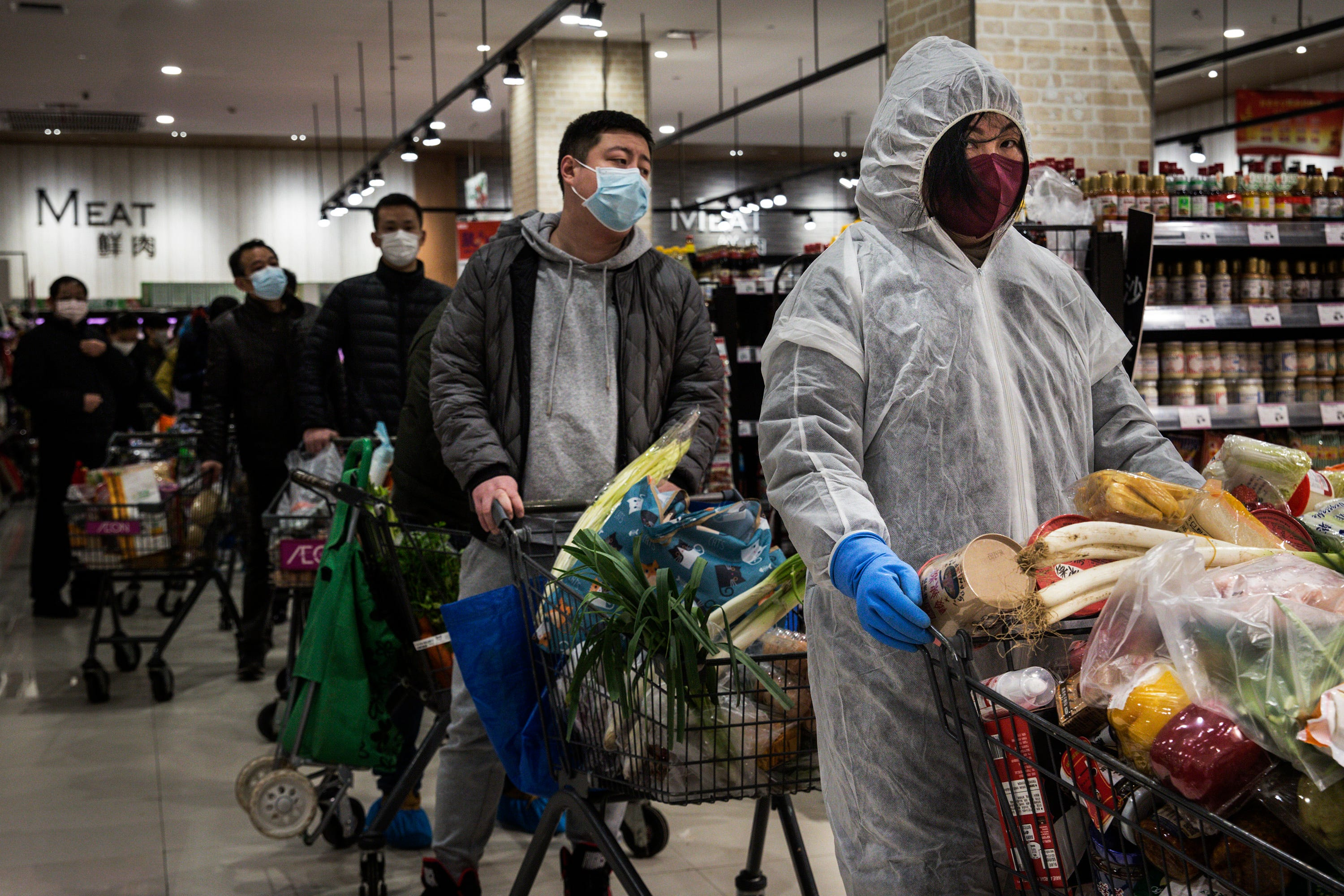 People wear protective masks as they line up in a supermarket on Feb. 12 in Wuhan, China.