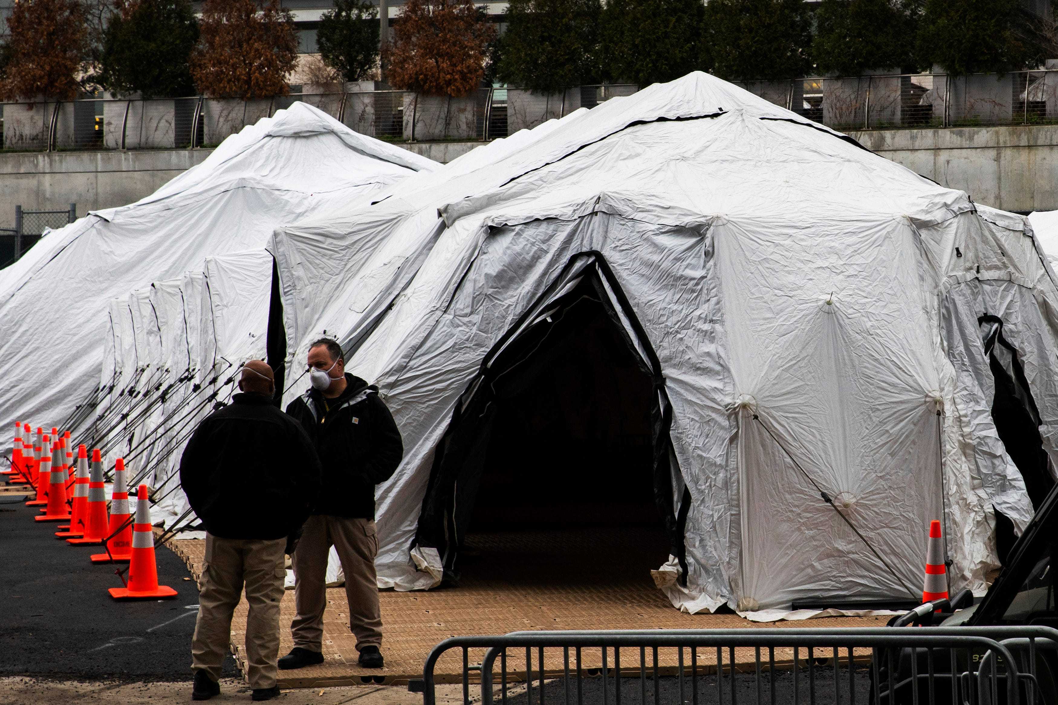 People speak near a makeshift morgue outside Bellevue Hospital on March 25 in New York City.