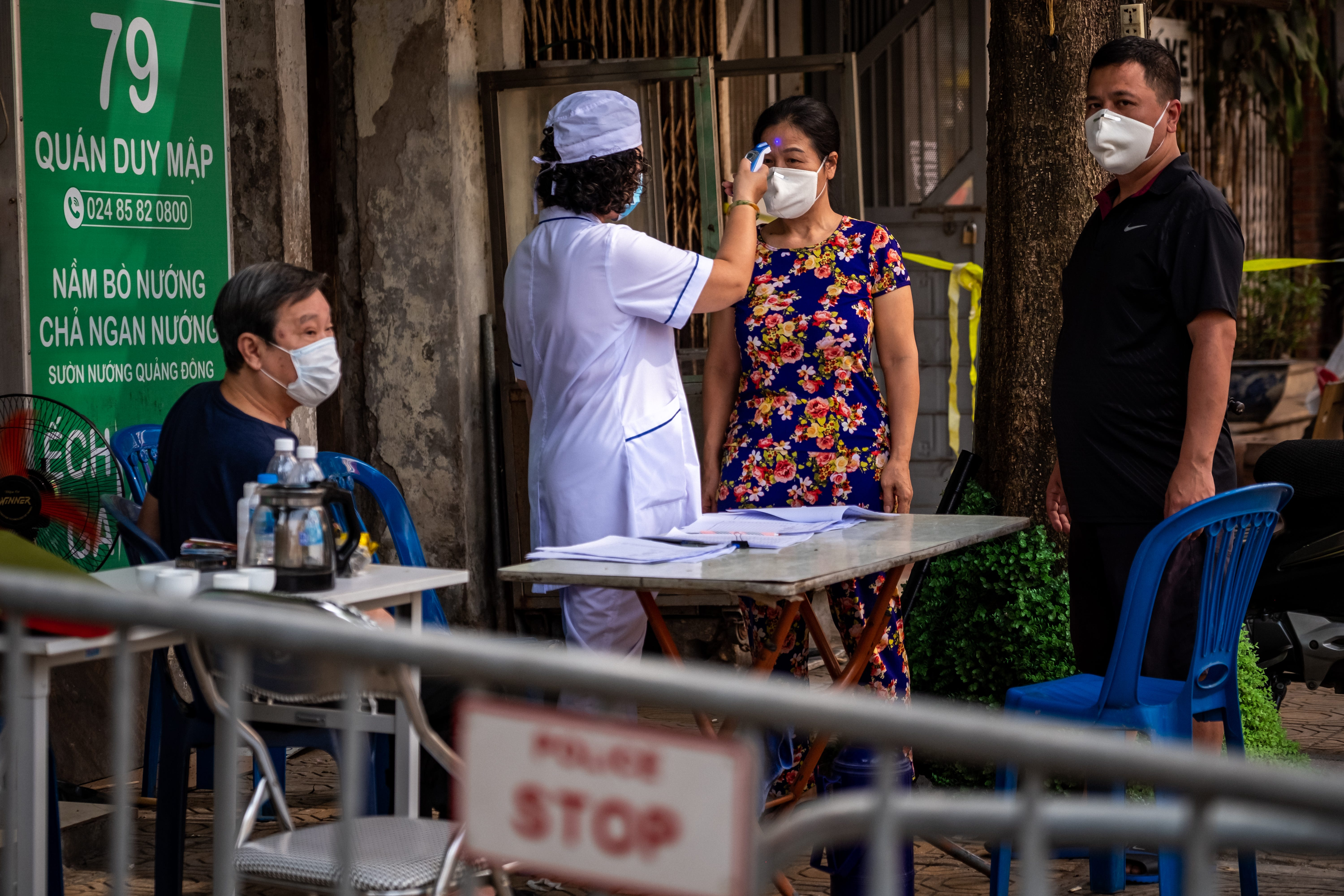 A health worker checks the temperatures of residents in the quarantined area of Truc Bach Street on March 9 in Hanoi. Authorities had blocked Truc Bach Street beginning March 6 to prevent the spread of COVID-19 after one resident, a 26-year-old Vietnamese woman recently back from Europe, contracted the virus.