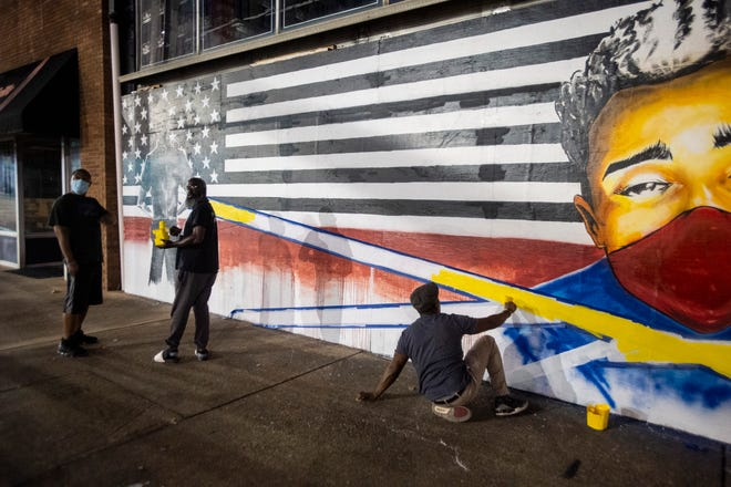 Milton Madison works on a mural on Montgomery Street in Montgomery, Ala., on Wednesday, Oct. 7, 2020.