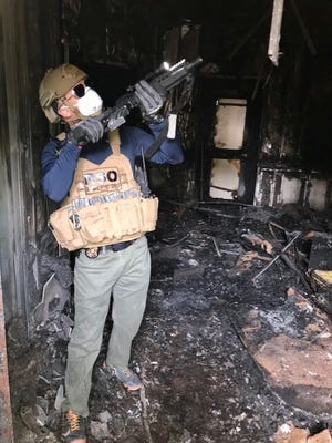 Special Agent Michael Ross checks one of the compound access control areas days after it had been burned by violent protestors during a Dec. 31 attack on the U.S. Embassy in Baghdad, Iraq.