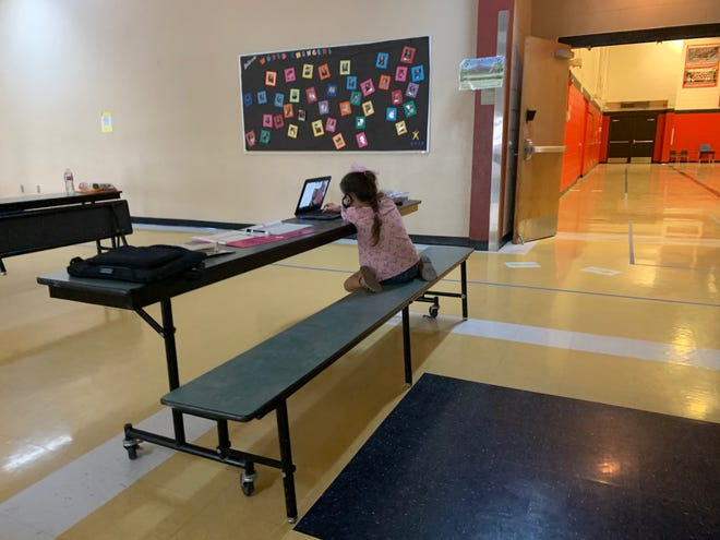A student focuses on class in a learning lab held in an Apache Junction school cafeteria.