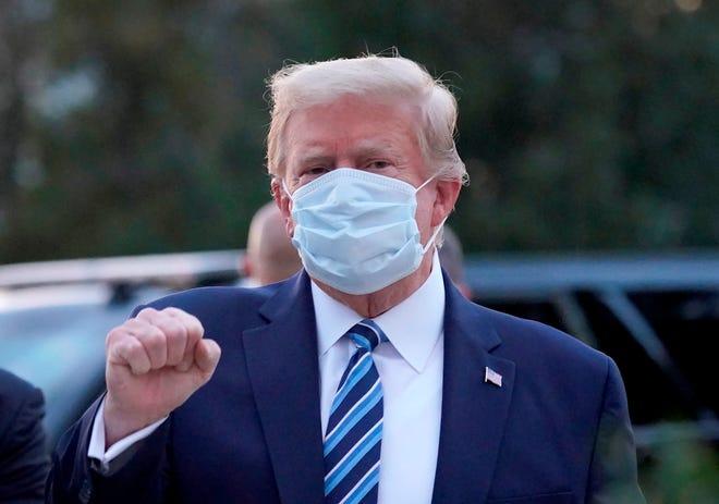 El presidente de Estados Unidos, Donald J. Trump, con una máscara, hace gestos después de salir del Centro Médico Militar Nacional Walter Reed, en Bethesda, Maryland, EE.UU.