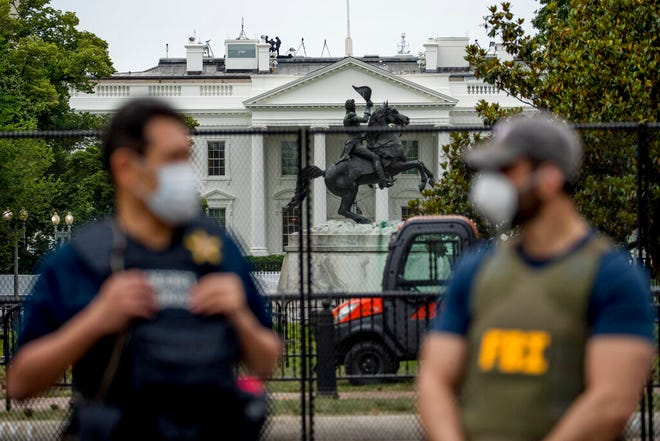 FILE - In this June 2, 2020, file photo the White House is visible behind a large security fence as uniformed Secret Service and FBI agents stand on the street in front of Lafayette Park in the morning hours in Washington. Federal and state law enforcement officials have begun expanded preparations for the possibility of widespread unrest at the polls on Election Day, a response to extraordinarily high tensions among voters and anxieties about safety stoked in part by President Donald Trump. (AP Photo/Andrew Harnik, File)