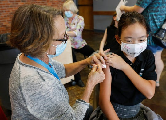 Lee Ann Neill, the coordinator of health services for Springfield Public Schools, gives fifth-grader Phoebe Lin a flu shot at the Discovery Center on Thursday, Oct. 8, 2020.