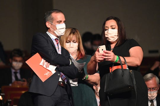 Los Angeles Mayor Eric Garcetti, left, wears a facemask as he arrives for the 2020 vice presidential debate.