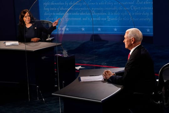 Vice President Mike Pence listens as Democratic vice presidential candidate Kamala Harris speaks during the vice presidential debate in Kingsbury Hall at the University of Utah on Wednesday.