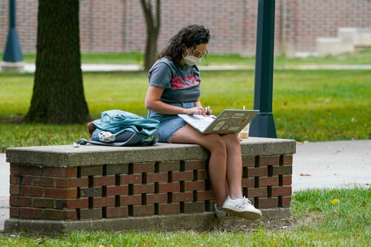 College students across the country need access to laptops to complete online learning this fall. At many community colleges, students are borrowing laptops to complete their coursework. Access to Wi-Fi remains an issue. Here, a Ball State University student works on the four-year campus in Muncie, Indiana.