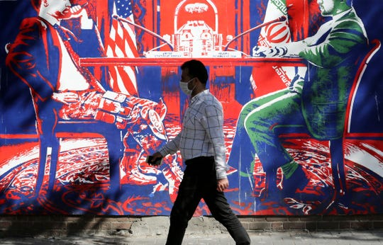 A man walks past a mural painted on the outer walls of the former U.S. embassy in the Iranian capital Tehran, on September 29, 2020.