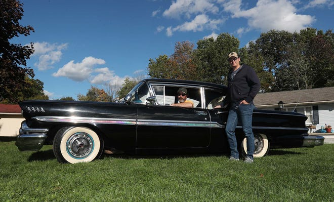 Paul Facemire sits in the driver's seat of his 1958 Chevy Biscayne next to his son Steve at his home in Doylestown. Steve spent years trying to track down his father's first car and finally found it through a broker in Wooster. [Karen Schiely/Beacon Journal]