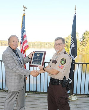 Dwight A. Holcomb, left, from the Ohio Attorney General's Office presents a lifetime achievement award to part-time Muskingum Watershed Park Ranger Matt Mayer, a retired Richland County Sheriff 's Office deputy, at Charles Mill Lake Marina and Campground on Thursday.