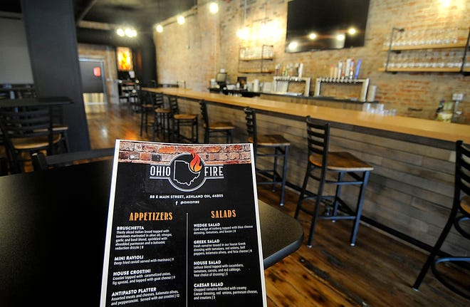 The dining room and bar at Ohio Fire Pizza, 88 E. Main St., along with its menu is shown here on Friday. The new downtown eatery will be opening on Monday, Oct. 12. The hours for the restaurant will be Monday through Saturday 11 a.m. to 10 p.m.