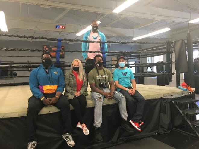 Members of the Solidarity Project team meeting at the Witherspoon Boxing & Fitness gym in Bristol Borough are (seated, from left) Justin Renfrow, Lisa Cochran, Bryant Watts and Michael Wilson.  Tim Witherspoon Jr., project president and gym owner, stands behind them.