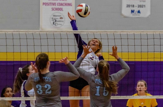 Hickman's Keely Henderson (2) goes for a spike over Tolton's Maggie McGuire (32) and Ellie Reynolds (15) during a match Thursday night at Hickman High School.
