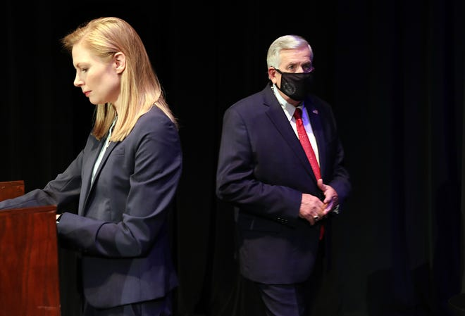 Gov. Mike Parson enters the stage, passing State Auditor Nicole Galloway before the Missouri gubernatorial debate at the Missouri Theatre in Columbia on Friday.