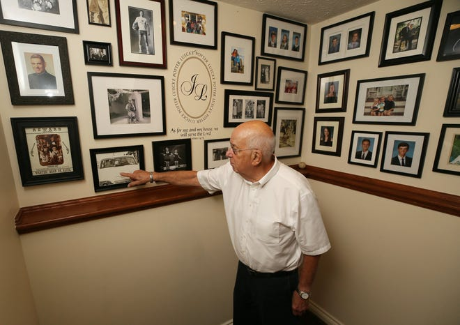 Jim Potter points to a photo of himself and his first wife, Judy, on their wedding day in 1961 on a wall of family photos in the home he shares with his second wife in Bay Village. Potter recalled how his father, a Democrat, switched party affiliation when FDR went for his third term in 1940.