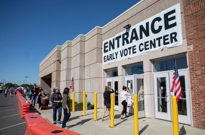 Voters wait in line at the Board of Elections for early voting in Columbus on Thursday, Oct. 8, 2020. The long line slinked around the building but moved very quickly. Voters on Thursday morning only had to wait about 10-15 minutes to get through the line.