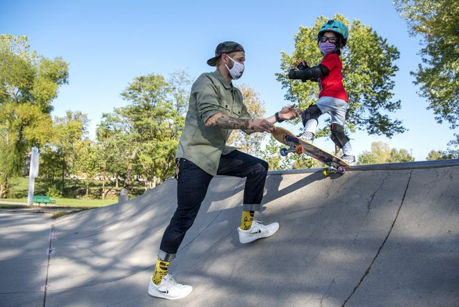Sora Chamberlain, 5, skateboards with his father, Tristan Chamberlain, at Adventure Park in Powell. The hobby has helped Sora, who has a rare genetic disorder, with his muscle tone and balance. [Gaelen Morse/Dispatch]