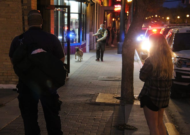 Thursday evening on North Main in downtown Crookston, a Polk County deputy brings his K-9 unit to assist in the search for a man in an apartment building. Looking on are, left, a Crookston Area Ambulance Service EMT, and a UMN Crookston student who first encountered the man in her apartment building. Her roommate called 911.