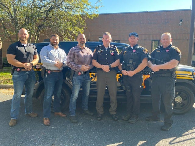 Guernsey County sheriff's deputies are wearing pink badges to raise awareness during Breast Cancer Awareness Month. Pictured wearing the badges are, l to r, detectives Sgt Bill Patterson, Aaron Coulter and Lt. Sam Williams; Sheriff Jeff Paden, Sgt. Robert Oakley and Major Jeremy S. Wilkinson.
