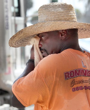 A construction worker with his shirt soaked, wipes sweat from his face with a towel under his big straw, Friday October 9, 2020 while pouring concrete on Beach Street.