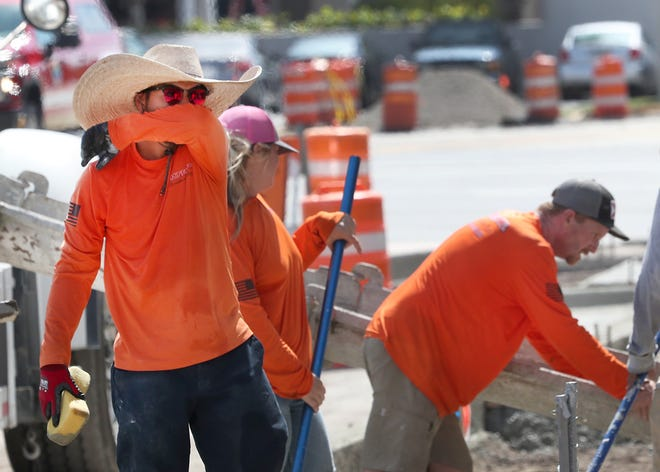 Construction workers on Beach Street in Daytona Beach battle the noon day heat on Friday. This past decade saw the hottest average temperature in Volusia County history, according to data from the weather service, while breaking multiple other heat records.