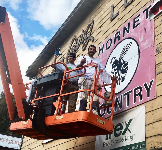 """Greg Edwards (left) and Brandon Seminario (right) donated their time and talents to refurbish the """"Hornet Country"""" sign that was originally put in place by the Honesdale Friends of Football booster club back in 1983."""