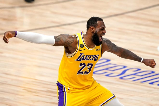 Los Angeles Lakers forward LeBron James celebrates Tuesday during the second half in Game 4 of the NBA Finals against the Miami Heat in Lake Buena Vista, Florida. [MARK J. TERRILL / AP]