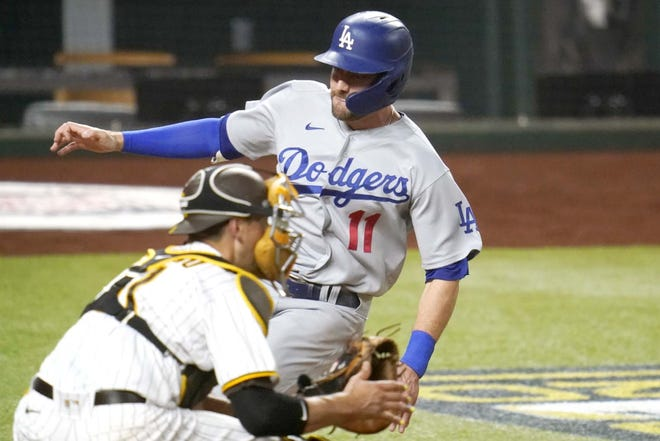 The Los Angeles Dodgers' A.J. Pollock (right) beats the throw to score on a hit by Joc Pederson during the third inning of Game 3 of their National League Division Series Thursday in Arlington, Texas. At left is San Diego Padres catcher Jason Castro. [SUE OGROCKI / AP]