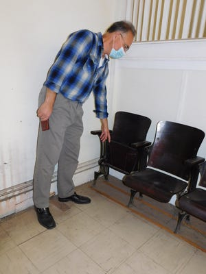 Joseph Chilelli points to the wire attachment for hat storage under a seat used in the opera house that once occupied the third floor of a building incorporated into Munger's Department Store in Herkimer.