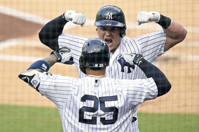 New York Yankee Luke Voit celebrates with Gleyber Torres (25) Thursday after Voit hit a solo home run against the Tampa Bay Rays during the second inning of Game 4 of an American League Division Series in San Diego. [GREGORY BULL / AP]