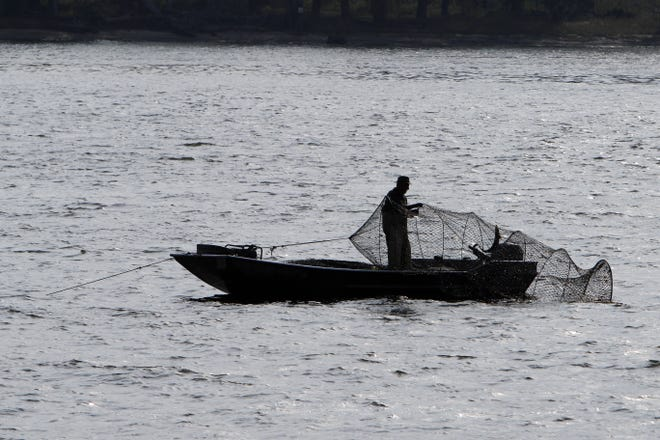 A fisherman is silhouetted while fishing, Friday Oct. 9, 2020 along the Mississippi River in Burlington. According the the Wisconsin DNR the Upper Mississippi River is home to over 119 species of fish.