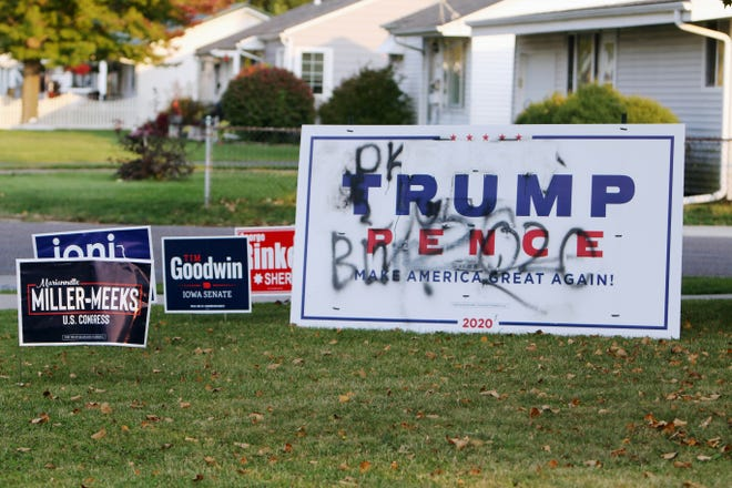 Elections signs in a yard including a vandalized Trump Pence sign, Thursday Oct. 8, 2020 in Burlington. According the homeowners, the sign was vandalized several weeks after they first put it out in their yard, after making repairs to the sign it was once again targeted. In addition to the vandalized sign the homeowners received a letter criticizing President Trump.