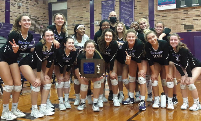 Fletcher's high school volleyball team celebrates with the Gateway Conference championship trophy after defeating Mandarin.