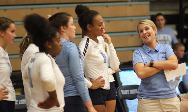 East Duplin volleyball coach Liz Howard, right, jokes with her team before a match last season. [Chris Miller / The Daily News]