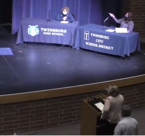 Superintendent Kathryn Powers talks about the district's financial needs to the school board. Behind her is Treasurer Martin Aho. Also pictured, on the stage, are board members Angela DeFabio, left, and Adrienne Gordon.