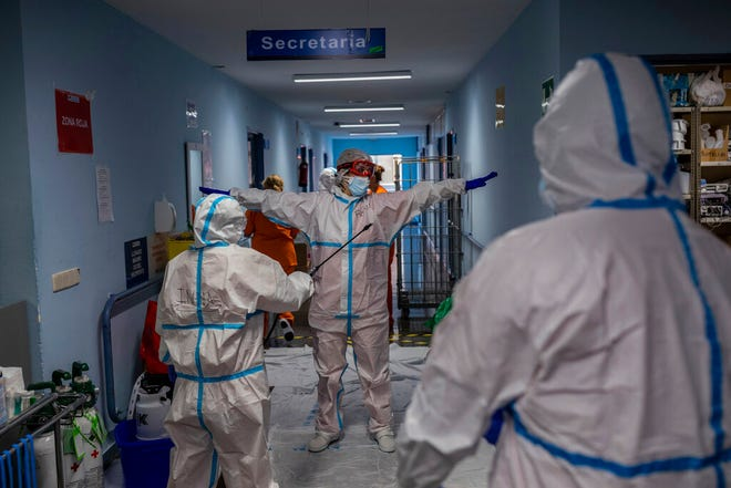 A medical team member is disinfected before leaving the COVID-19 ward at the Severo Ochoa hospital in Leganes, outskirts of Madrid, Spain, Friday, Oct. 9, 2020. At the peak of the first wave, ICU wards were given over to haste, desperation and even cluelessness about what to do. Now, a well-oiled machinery saves some lives and loses others to coronavirus, but without the doomsday atmosphere of March and April.