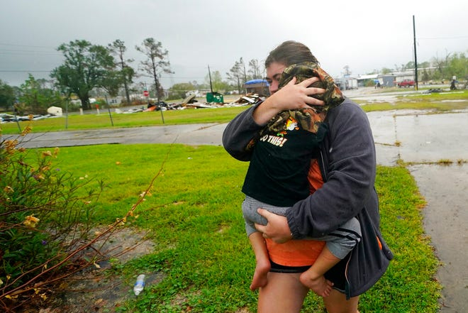 Danielle Fontenot runs to a relative's home in the rain with her son Hunter ahead of Hurricane Delta, Friday, Oct. 9, 2020, in , La. Forecasters said Delta — the 25th named storm of an unprecedented Atlantic hurricane season — would likely crash ashore Friday evening somewhere on southwest Louisiana's coast.