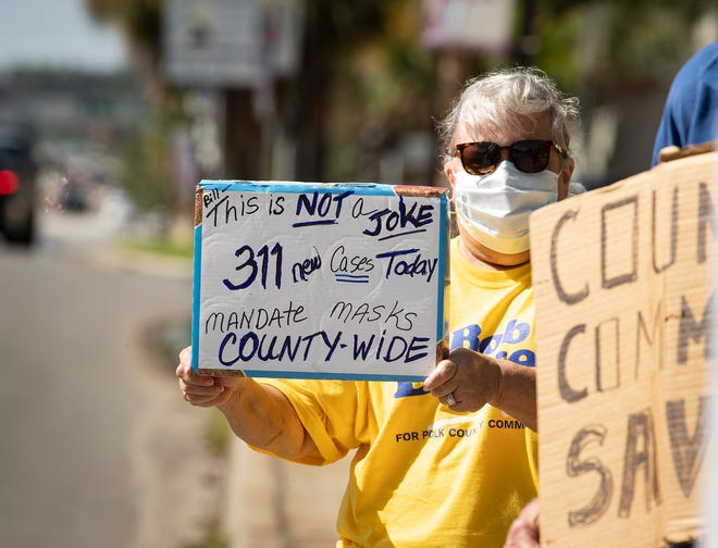 Karen Welzel holds a sign advocating for mandatory mask wearing  in front of the Historical Polk County Courthouse in Bartow on July 9. A months-long struggle between pro- and anti-mask groups across the county is ending as city ordinances are being allowed to expire as Polk opens up during the COVID-19 pandemic.