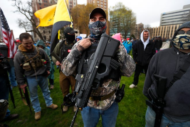 A protester carries his rifle at the State Capitol in Lansing, Mich. A plot to kidnap Michigan's governor has put a focus on the security of governors who have faced protests and threats over their handling of the coronavirus pandemic.