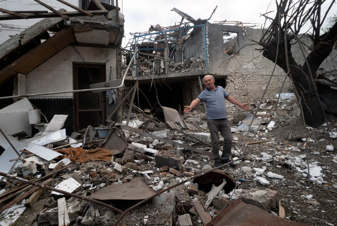 A man gestures in the yard of a house destroyed by shelling by Azerbaijan's artillery during a military conflict in Stepanakert, the separatist region of Nagorno-Karabakh, on Friday.